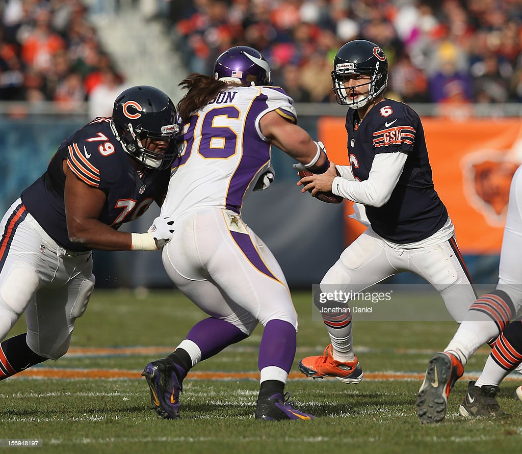 Jay Cutler #6 of the Chicago Bears looks for a receiver as teammate Jonathan Scott #79 blocks Brian Robinson #96 of the Minnesota Vikings at Soldier Field on November 25, 2012 in Chicago, Illinois. The Bears defeated the Vikings 28-10.