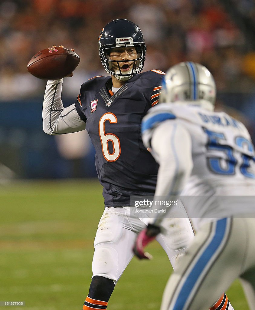 Jay Cutler of the Chicago Bears throws a touchdown pass under pressure from Justin Durant of the Detroit Lions at Soldier Field on October 22 2012 in...