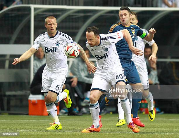 Jay DeMerit and Andy O'Brien of the Vancouver Whitecaps FC and Robbie Keane of the Los Angeles Galaxy chase a loose ball during their MLS game April...