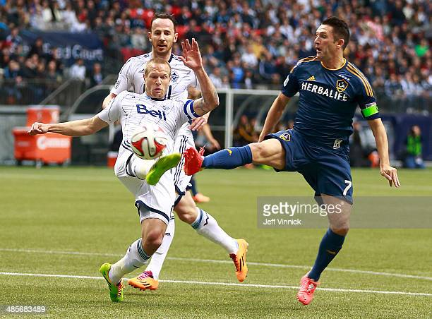 Jay DeMerit of the Vancouver Whitecaps FC and Robbie Keane of the Los Angeles Galaxy battle for the ball during their MLS game April 19 2014 in...