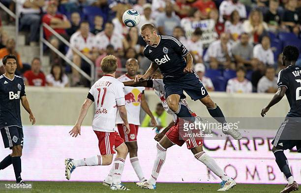 Jay DeMerit of the Vancouver Whitecaps FC heads the ball against Dax McCarty and Juan Agudelo of the New York Red Bulls at Red Bull Arena on...
