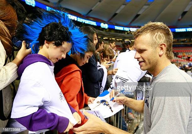 Jay DeMerit of the Vancouver Whitecaps FC signs autographs for fans during their MLS game against the Portland Timbers October 21 2012 at BC Place in...