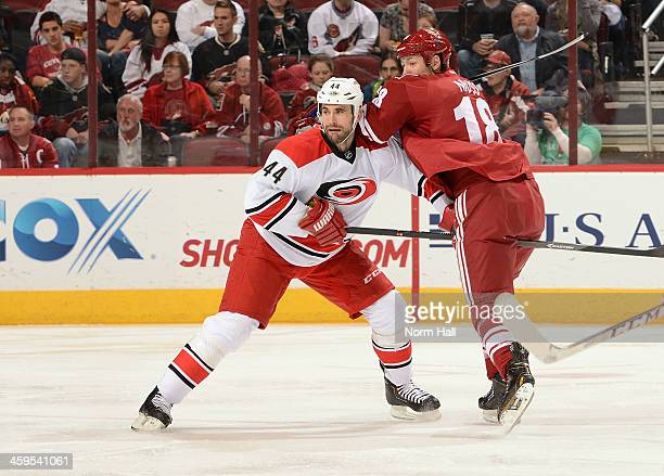 Jay Harrison of the Carolina Hurricanes battles for position with David Moss of the Phoenix Coyotes at Jobingcom Arena on December 14 2013 in...