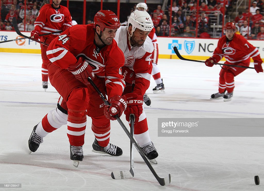 <a gi-track='captionPersonalityLinkClicked' href=/galleries/search?phrase=Jay+Harrison&family=editorial&specificpeople=714374 ng-click='$event.stopPropagation()'>Jay Harrison</a> #44 of the Carolina Hurricanes battles for the puck with <a gi-track='captionPersonalityLinkClicked' href=/galleries/search?phrase=Todd+Bertuzzi&family=editorial&specificpeople=202476 ng-click='$event.stopPropagation()'>Todd Bertuzzi</a> #44 of the Detroit Red Wings during an NHL game on October 4, 2013 in the home opener at PNC Arena in Raleigh, North Carolina.