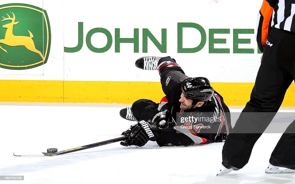 Jay Harrison #44 of the Carolina Hurricanes collects the puck while down on the ice during an NHL game against the Washington Capitals at PNC Arena on March 14, 2013 in Raleigh, North Carolina.