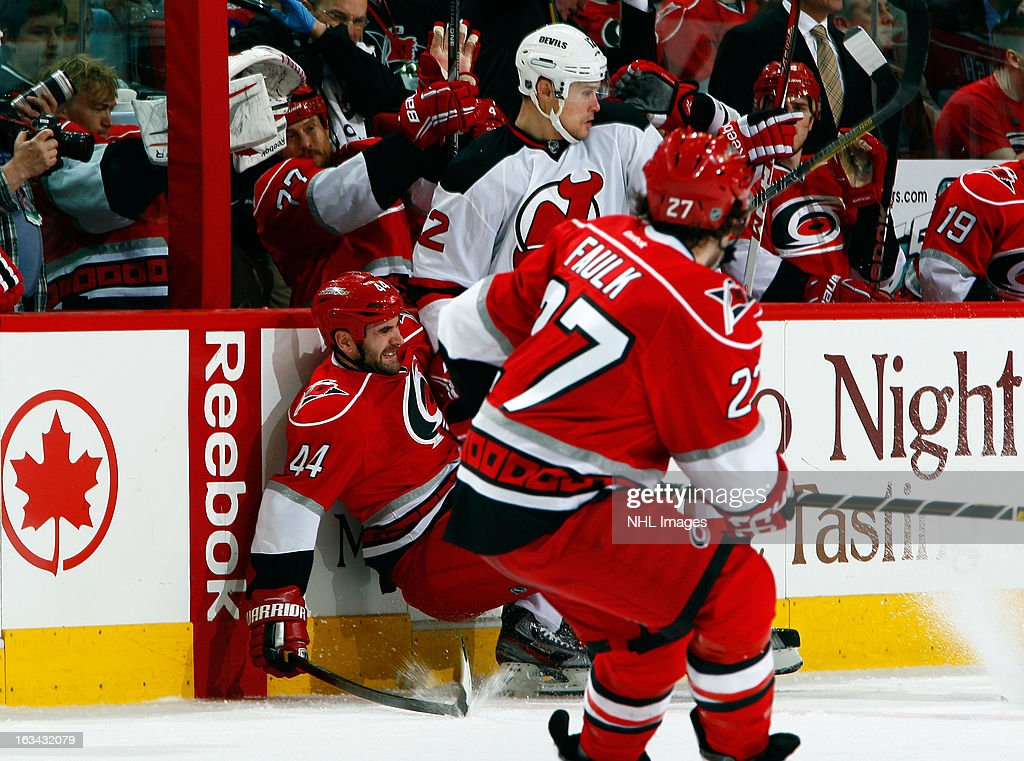 Jay Harrison #44 of the Carolina Hurricanes is knocked to the ice by <a gi-track='captionPersonalityLinkClicked' href=/galleries/search?phrase=Alexei+Ponikarovsky&family=editorial&specificpeople=210628 ng-click='$event.stopPropagation()'>Alexei Ponikarovsky</a> #12 of the New Jersey Devils as Justin Faulk #27 looks on during an NHL game on March 9, 2013 at PNC Arena in Raleigh, North Carolina.