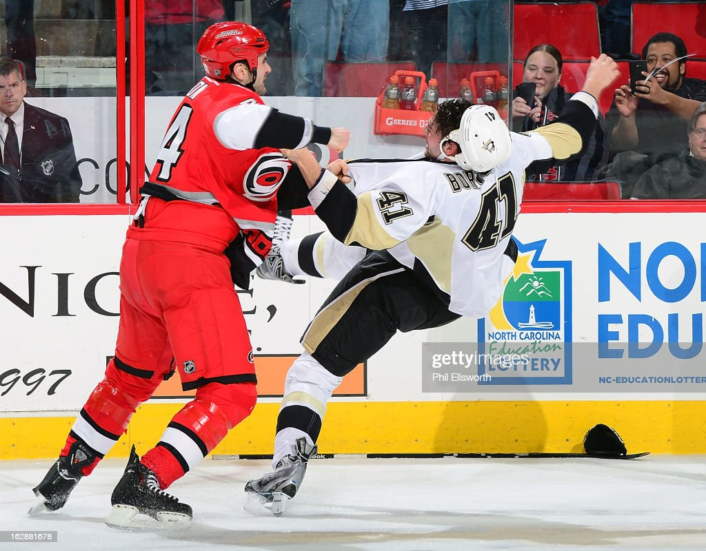 Jay Harrison #44 of the Carolina Hurricanes lands a punch, knocking Robert Bortuzzo #41 of the Pittsburgh Penguins off balance and to the ice during an NHL game on February 28, 2013 at PNC Arena in Raleigh, North Carolina.