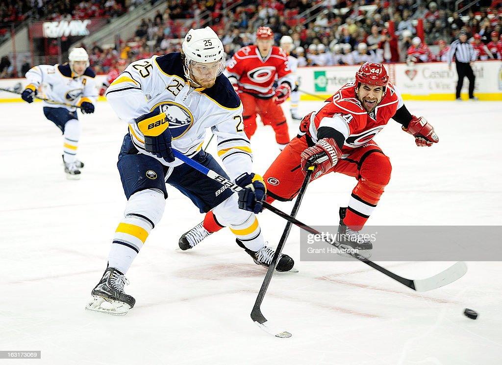 Jay Harrison #44 of the Carolina Hurricanes pokes the puck away from <a gi-track='captionPersonalityLinkClicked' href=/galleries/search?phrase=Mikhail+Grigorenko&family=editorial&specificpeople=8771251 ng-click='$event.stopPropagation()'>Mikhail Grigorenko</a> #25 of the Buffalo Sabres during play at PNC Arena on March 5, 2013 in Raleigh, North Carolina.