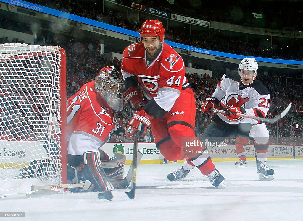Jay Harrison #44 of the Carolina Hurricanes takes care of a loose puck at right of goaltender <a gi-track='captionPersonalityLinkClicked' href=/galleries/search?phrase=Dan+Ellis&family=editorial&specificpeople=2235265 ng-click='$event.stopPropagation()'>Dan Ellis</a> #31 as <a gi-track='captionPersonalityLinkClicked' href=/galleries/search?phrase=Andrei+Loktionov&family=editorial&specificpeople=5370946 ng-click='$event.stopPropagation()'>Andrei Loktionov</a> #21 of the New Jersey Devils looks on during an NHL game on March 9, 2013 at PNC Arena in Raleigh, North Carolina.