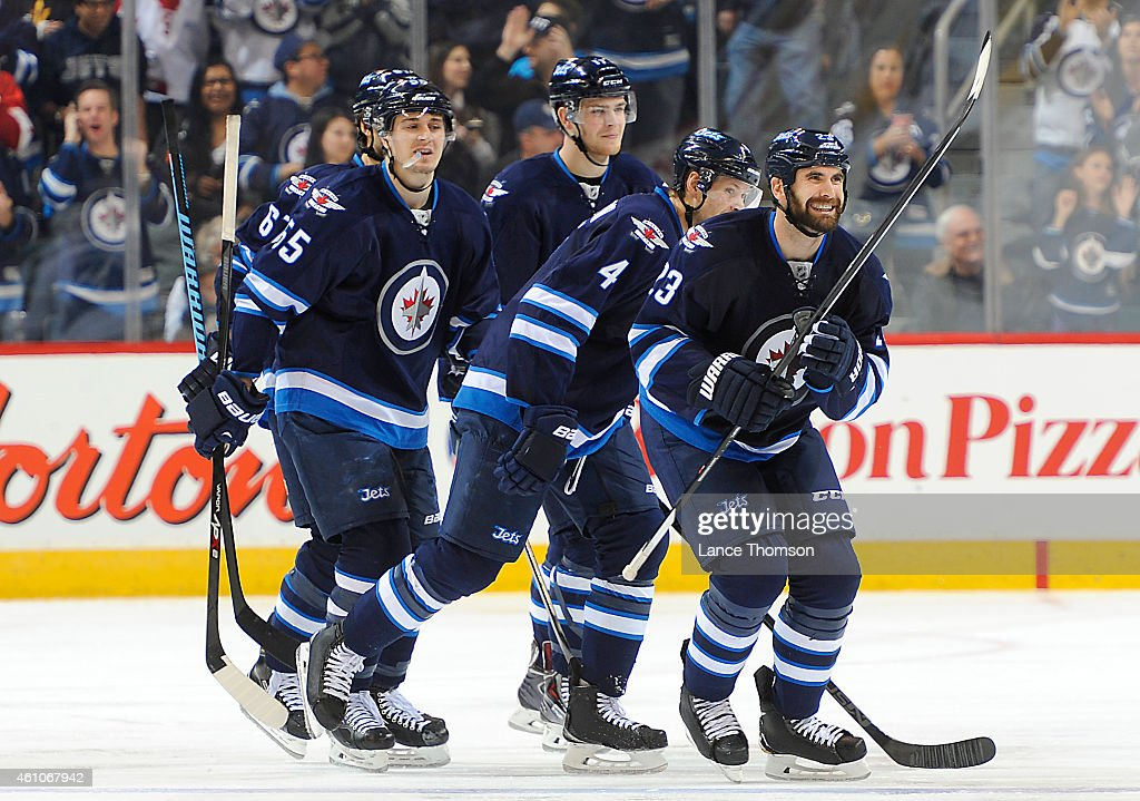<a gi-track='captionPersonalityLinkClicked' href=/galleries/search?phrase=Jay+Harrison&family=editorial&specificpeople=714374 ng-click='$event.stopPropagation()'>Jay Harrison</a> #23 of the Winnipeg Jets is all smiles as he leads teammates to the bench after scoring his first goal as a Jet during third period action against the San Jose Sharks on January 5, 2015 at the MTS Centre in Winnipeg, Manitoba, Canada.