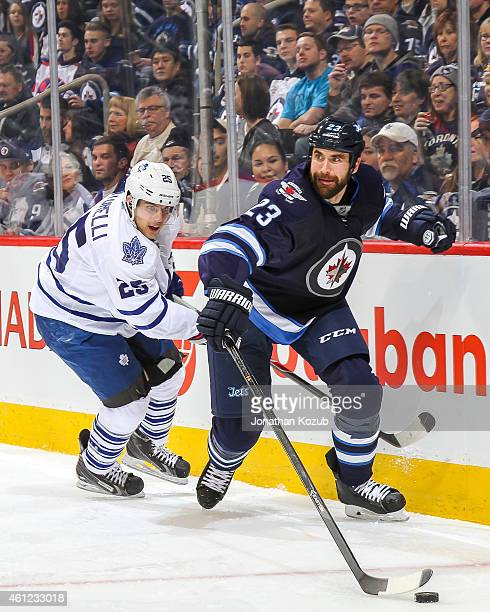 Jay Harrison of the Winnipeg Jets plays the puck away from Mike Santorelli of the Toronto Maple Leafs during second period action on January 3 2015...