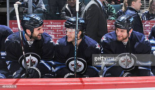 Jay Harrison Toby Enstrom and Adam Pardy of the Winnipeg Jets share a laugh on the bench prior to puck drop against the Dallas Stars on February 24...