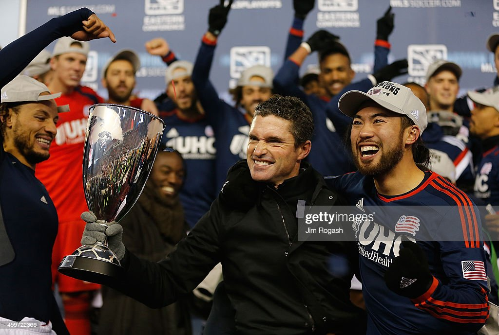 Jay Heaps coach of New England Revolution holds the trophy as the team celebrates after defeating the New York Red Bulls the MLS Eastern Conference...