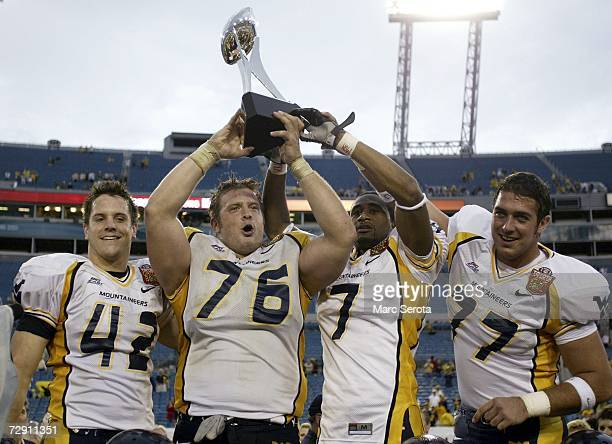 Jay Henry Dan Mozes Brandon Myles and Tim Lindsey of the West Virginia Mountaineers holds up the trophy after defeating the Georgia Tech Yellow...