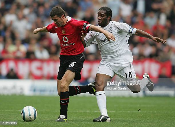 Jay Jay Okocha of Bolton clashes with Roy Keane of Man Utd during the Barclays Premiership match between Bolton Wanderers and Manchester United at...