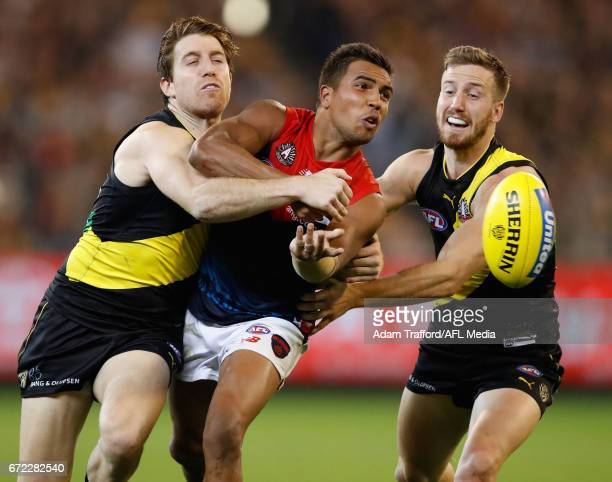 Jay KennedyHarris of the Demons is tackled by Reece Conca and Kane Lambert of the Tigers during the 2017 AFL round 05 match between the Richmond...