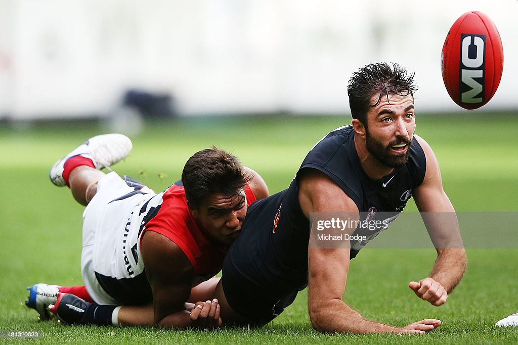 Jay Kennedy-Harris tackles Kade Simpson of the Blues during the round four AFL match between the Carlton Blues and the Melbourne Demons at Melbourne Cricket Ground on April 12, 2014 in Melbourne, Australia.