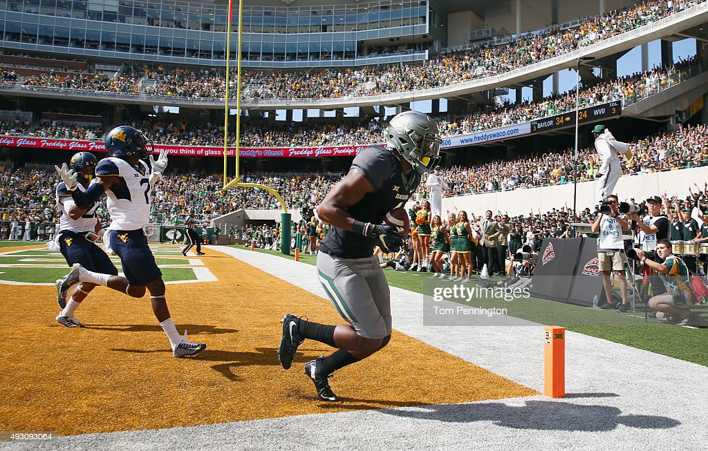 Jay Lee of the Baylor Bears pulls in a touchdown pass in the end zone against Jarrod Harper of the West Virginia Mountaineers and Daryl Worley of the...