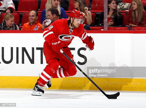 Jay Mc Clement of the Carolina Hurricanes skates with the puck along the boards during their NHL game against the New York Islanders at PNC Arena on...