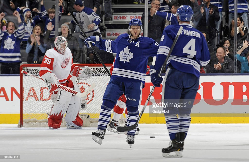 Jay McClement #11 and Cody Franson #4 of the Toronto Maple Leafs celebrate a first period goal as Jimmy Howard #35 of the Detroit Red Wings looks on during NHL game action March 29, 2014 at the Air Canada Centre in Toronto, Ontario, Canada.