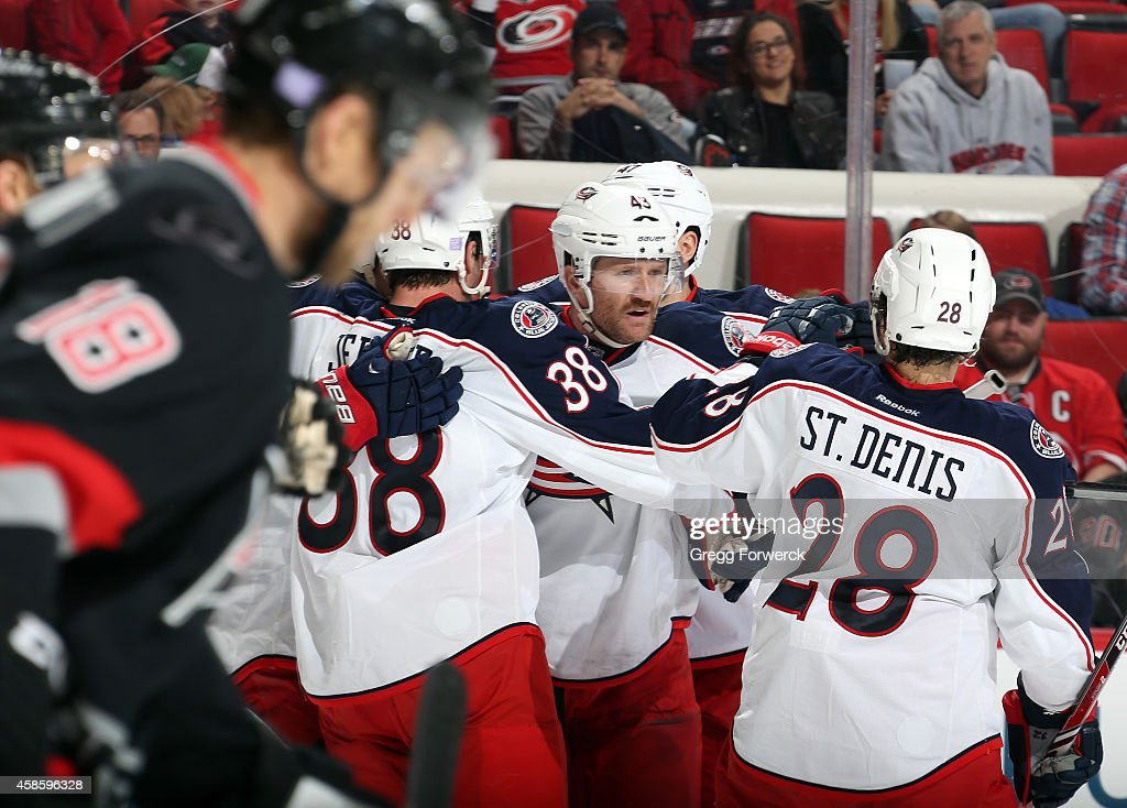 Jay McClement of the Carolina Hurricanes skates toward the bench as Scott Hartnell of the Columbus Blue Jackets celebrates his first goal of the...