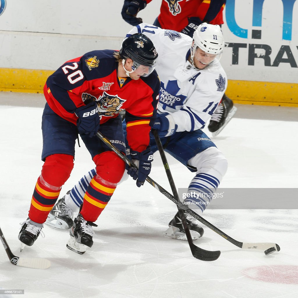 <a gi-track='captionPersonalityLinkClicked' href=/galleries/search?phrase=Jay+McClement&family=editorial&specificpeople=575233 ng-click='$event.stopPropagation()'>Jay McClement</a> #11 of the Toronto Maple Leafs attempts to check the puck away from <a gi-track='captionPersonalityLinkClicked' href=/galleries/search?phrase=Sean+Bergenheim&family=editorial&specificpeople=208830 ng-click='$event.stopPropagation()'>Sean Bergenheim</a> #20 of the Florida Panthers during third-period action at the BB&T Center on February 4, 2014 in Sunrise, Florida. The Panthers defeated the Maple Leafs 4-1.