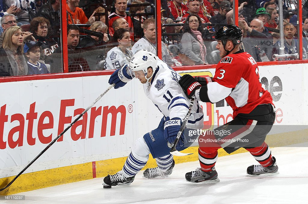 Jay McClement #11 of the Toronto Maple Leafs beats Marc Methot #3 of Ottawa Senators to the loose puck during an NHL game, at Scotiabank Place, on April 20, 2013 in Ottawa, Ontario, Canada.