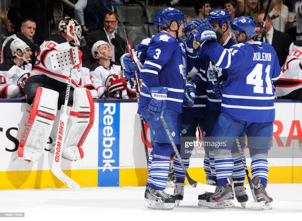 Jay McClement #11 of the Toronto Maple Leafs celebrates a third period empty net goal with teammates as goalie Martin Brodeur #30 of the New Jersey Devils climbs over the boards during NHL game action April 15, 2013 at the Air Canada Centre in Toronto, Ontario, Canada.