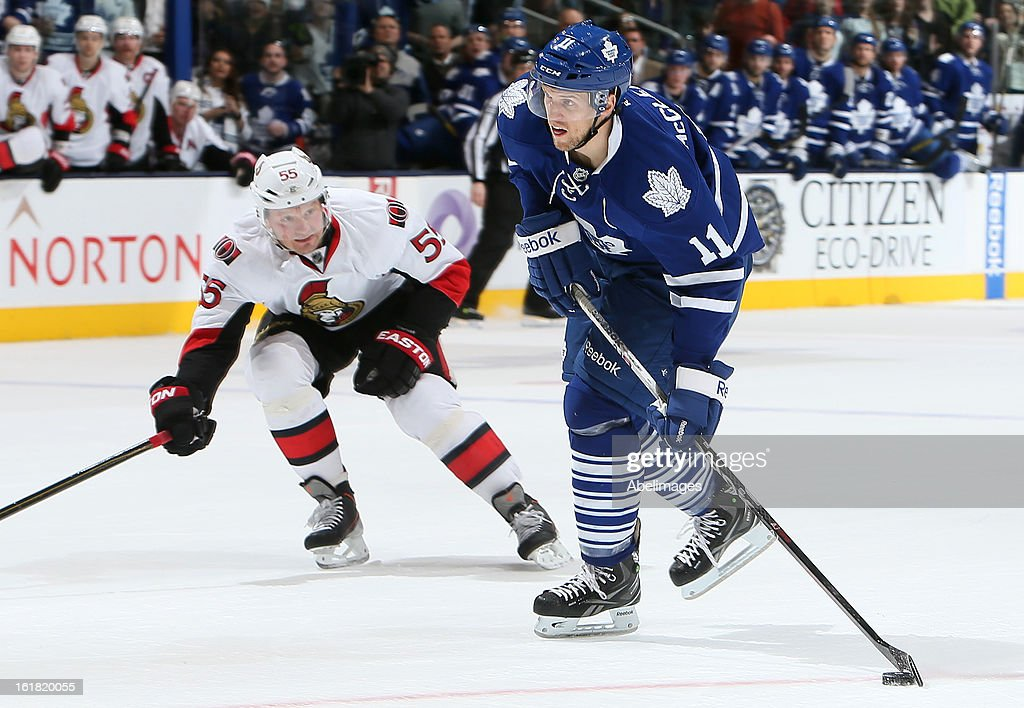 Jay McClement #11 of the Toronto Maple Leafs shoots past <a gi-track='captionPersonalityLinkClicked' href=/galleries/search?phrase=Sergei+Gonchar&family=editorial&specificpeople=202470 ng-click='$event.stopPropagation()'>Sergei Gonchar</a> #55 of the Ottawa Senators during NHL action at the Air Canada Centre February 16, 2013 in Toronto, Ontario, Canada.