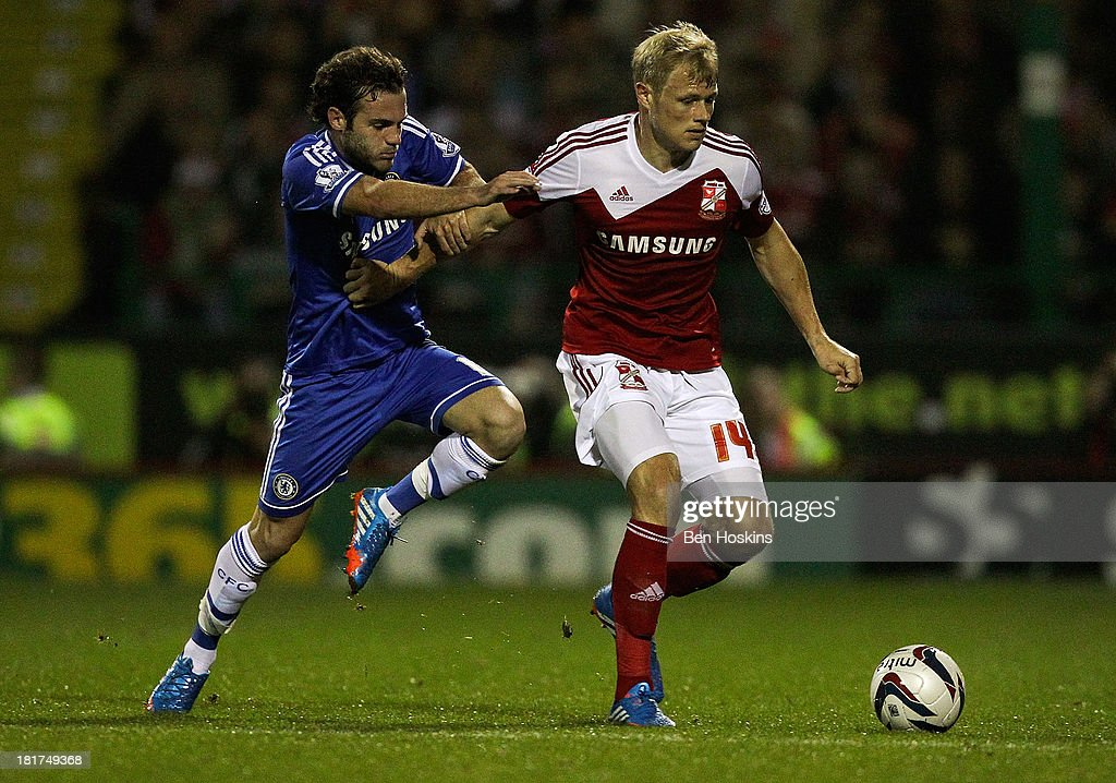 Jay McEveley of Swindon holds off pressure from <a gi-track='captionPersonalityLinkClicked' href=/galleries/search?phrase=Juan+Mata&family=editorial&specificpeople=4784696 ng-click='$event.stopPropagation()'>Juan Mata</a> of Chelsea during the Capital One Cup third round match between Swindon Town and Chelsea at County Ground on September 24, 2013 in Swindon, England.