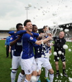 Jay O'Shea of Chesterfield celebrating their promotion with champagne during the Sky Bet League Two match between Burton Albion and Chesterfield at...