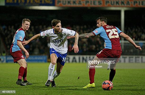 Jay O'Shea of Chesterfield goes past Andrew Boyce of Scunthorpe during the FA Cup Third Round match between Scunthorpe United and Chesterfield FC at...