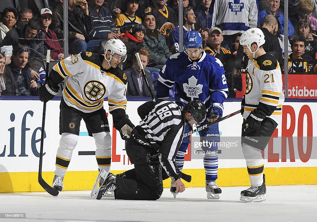 Jay Pandolfo #29 and Andrew Ference of the Boston Bruins along with John-Michael Liles #24 of the Toronto Maple Leafs check on Linesman Steve Miller after during a break in NHL game action March 23, 2013 at the Air Canada Centre in Toronto, Ontario, Canada.