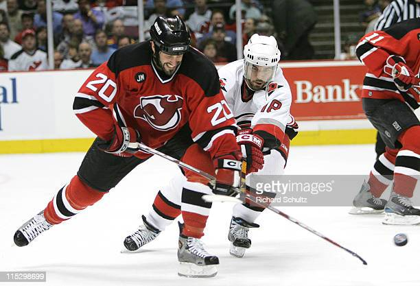 Jay Pandolfo of the New Jersey Devils battles Mark Recchi of the Carolina Hurricanes for the puck during the second period of game three in the...