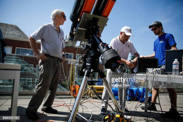 Jay Pasachoff left talks to Michael Person center and Aaron Sliski right as they set up a large telescope to observe the upcoming solar eclipse at...