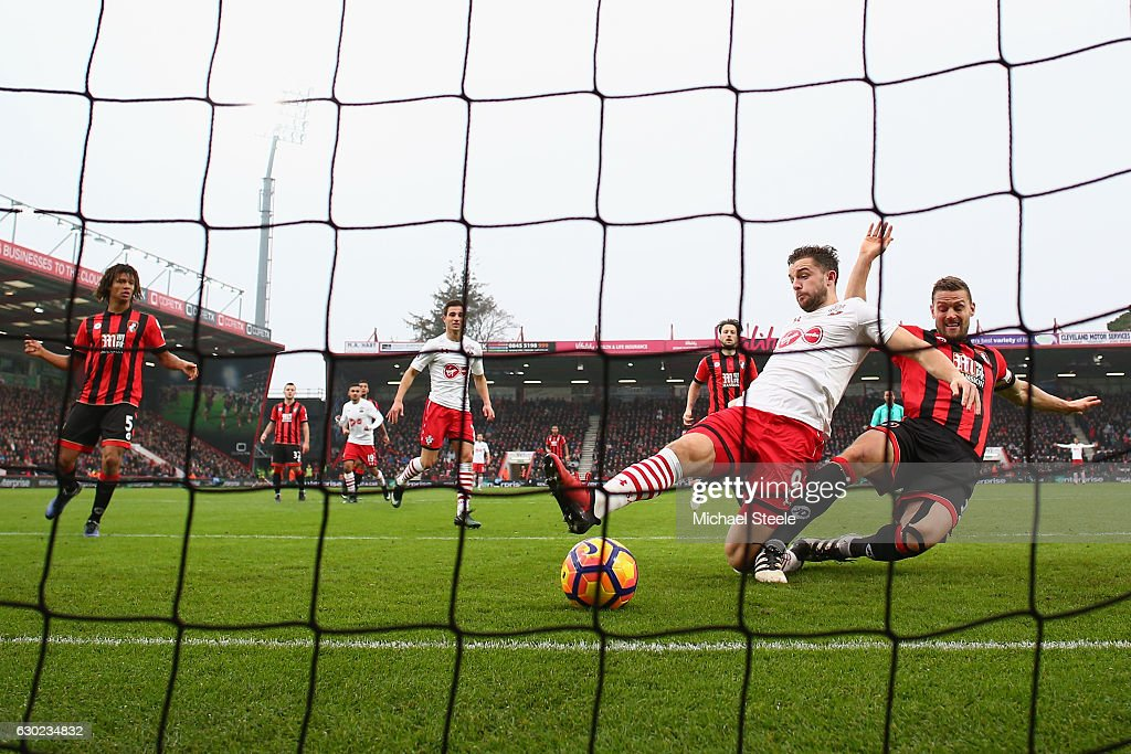 Jay Rodriguez of Southampton (C) scores his sides second goal despite the challenge of Simon Francis of Bournemouth during the Premier League match between AFC. Bournemouth and Southampton at the Vitality Stadium on December 18, 2016 in Bournemouth, England.