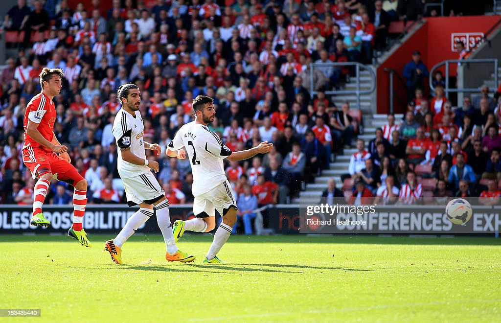 Jay Rodriguez of Southampton (9) shoots past Chico Flores (C) and <a gi-track='captionPersonalityLinkClicked' href=/galleries/search?phrase=Jordi+Amat&family=editorial&specificpeople=5534311 ng-click='$event.stopPropagation()'>Jordi Amat</a> of Swansea City (R) to score their second goal during the Barclays Premier League match between Southampton and Swansea City at St Mary's Stadium on October 6, 2013 in Southampton, England.