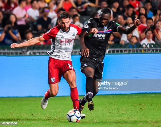 Jay Rodriguez of West Bromwich Albion fights for the ball with Christian Benteke of Crystal Palace during the thirdplace playoff match of the Premier...