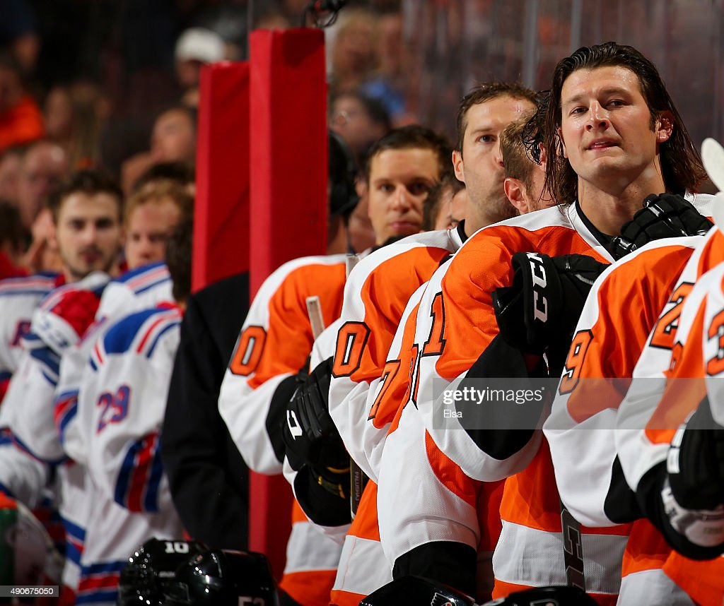 Jay Rosehill of the Philadelphia Flyers and the rest of his teammates stand on the bench for the national anthem before the game against the New York...