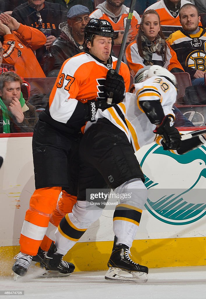 Jay Rosehill of the Philadelphia Flyers collides with Jordan Caron of the Boston Bruins at the Wells Fargo Center on January 25 2014 in Philadelphia...