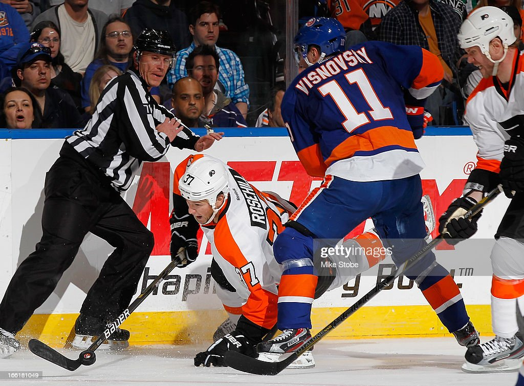 Jay Rosehill #37 of the Philadelphia Flyers falls to the ice in front of Lubomir Visnovsky #11 of the New York Islanders at Nassau Veterans Memorial Coliseum on April 9, 2013 in Uniondale, New York. The Islanders defeated the Flyers 4-1.
