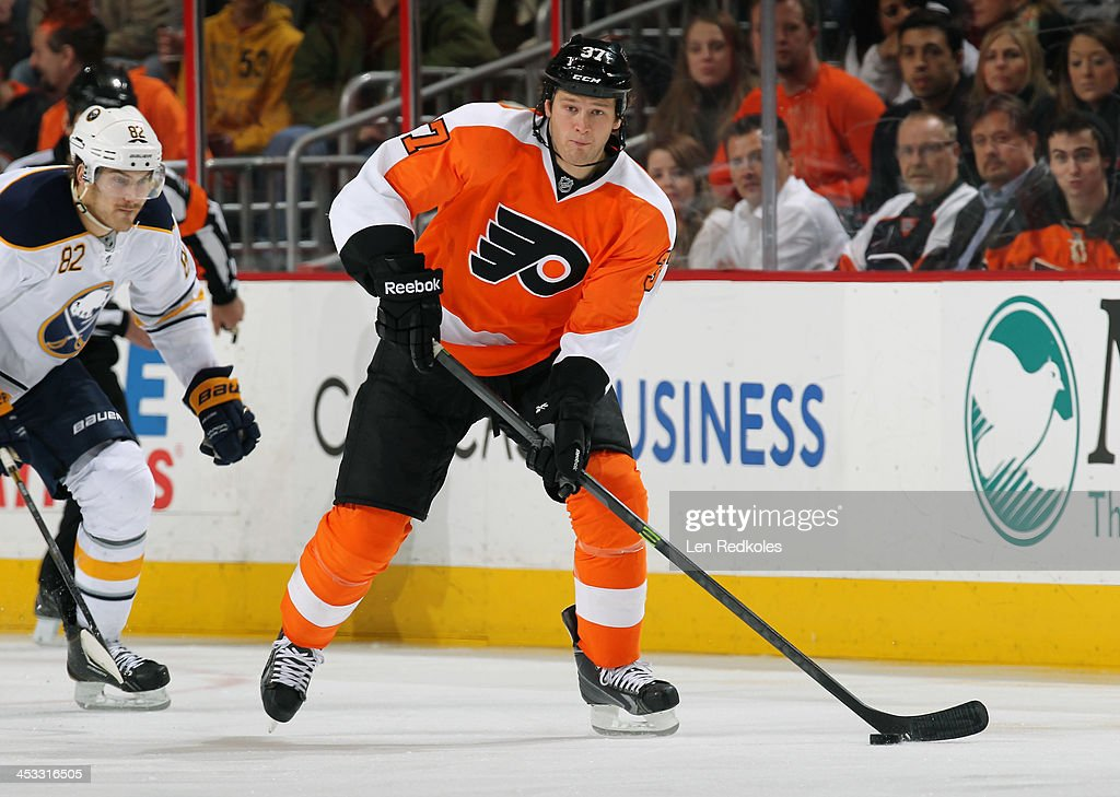 Jay Rosehill of the Philadelphia Flyers skates the puck against Marcus Foligno of the Buffalo Sabres on November 21 2013 at the Wells Fargo Center in...