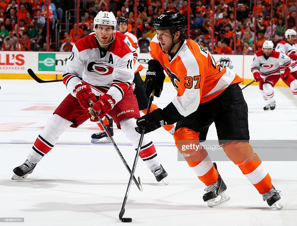 Jay Rosehill of the Philadelphia Flyers takes the puck as Jordan Staal of the Carolina Hurricanes defends in the second period at Wells Fargo Center...