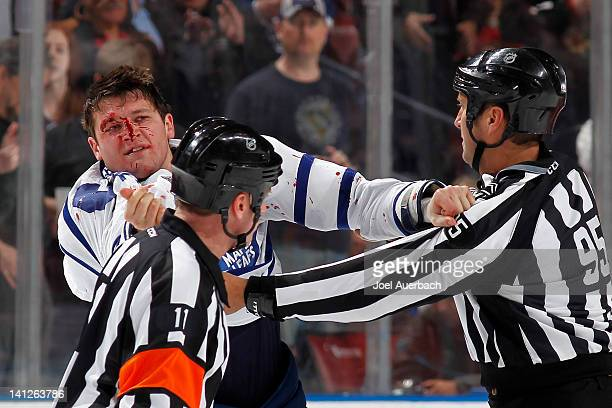 Jay Rosehill of the Toronto Maple Leafs is held back by linesman Jonny Murray after having his face bloodied in a fight with Krys Barch of the...