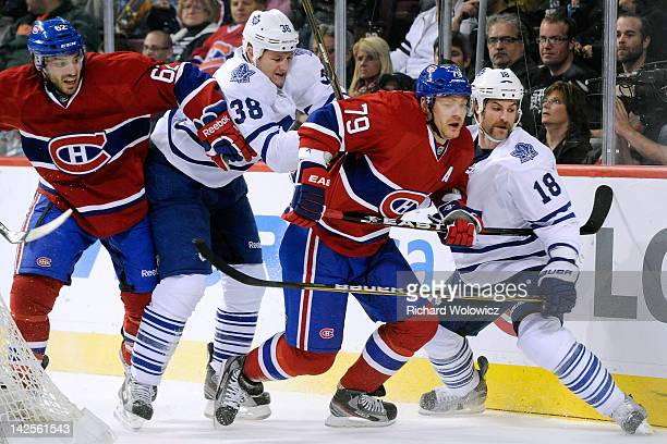 Jay Rosehill of the Toronto Maple Leafs shoves Andrei Markov of the Montreal Canadiens from behind during the NHL game at the Bell Centre on April 7...