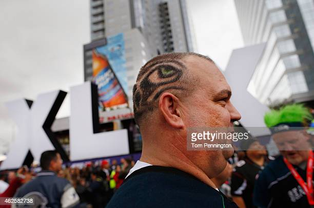 Jay Russell walks past the logo for the upcoming Super Bowl XLIX between the Seattle Seahawks and New England Patriots in an NFL fan zone on January...