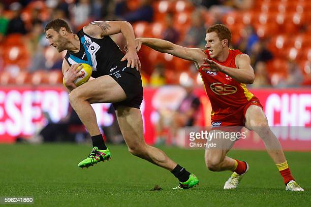 Jay Shultz of the Power runs the ball during the round 23 AFL match between the Gold Coast Suns and the Port Adelaide Power at Metricon Stadium on...