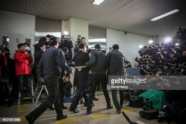 Jay Y Lee covice chairman of Samsung Electronics Co center left is escorted by police officers as he arrives at the special prosecutors' office in...