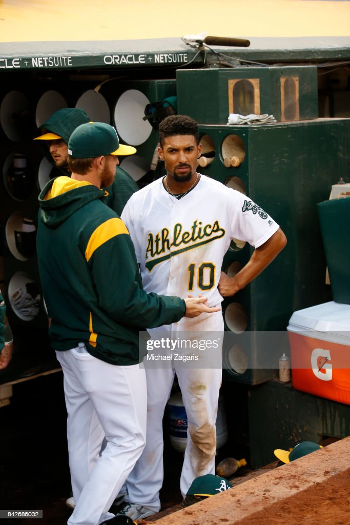 Jaycob Brugman #38 and Marcus Semien #10 of the Oakland Athletics talk in the dugout during the game against the Kansas City Royals at the Oakland Alameda Coliseum on August 14, 2017 in Oakland, California. The Royals defeated the Athletics 6-2.