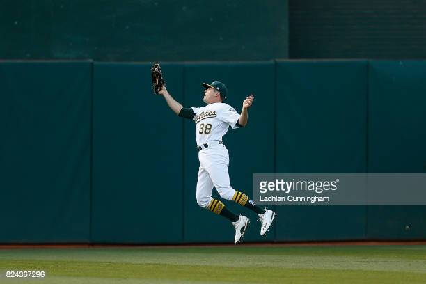 Jaycob Brugman of the Oakland Athletics catches a fly ball hit by Robbie Grossman of the Minnesota Twins in the fifth inning at Oakland Alameda...